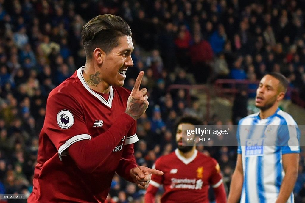 Liverpool's Brazilian midfielder Roberto Firmino celebrates scoring their second goal during the English Premier League football match between Huddersfield Town and Liverpool at the John Smith's stadium in Huddersfield, northern England on January 30, 2018. / AFP PHOTO / PAUL ELLIS / RESTRICTED TO EDITORIAL USE. No use with unauthorized audio, video, data, fixture lists, club/league logos or 'live' services. Online in-match use limited to 75 images, no video emulation. No use in betting, games or single club/league/player publications. /