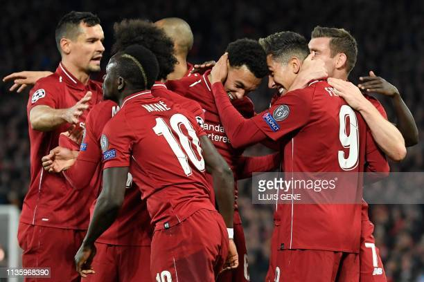 TOPSHOT Liverpool's Brazilian midfielder Roberto Firmino celebrates with teammates after scoring a goal during the UEFA Champions League quarterfinal...