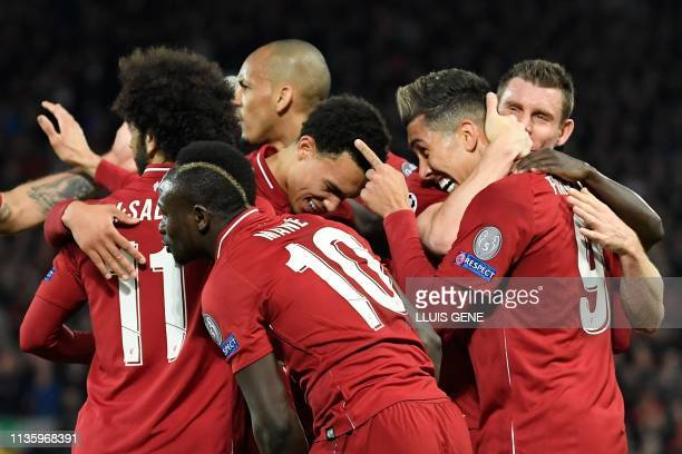 Liverpool's Brazilian midfielder Roberto Firmino celebrates with teammates after scoring a goal during the UEFA Champions League quarterfinal first...