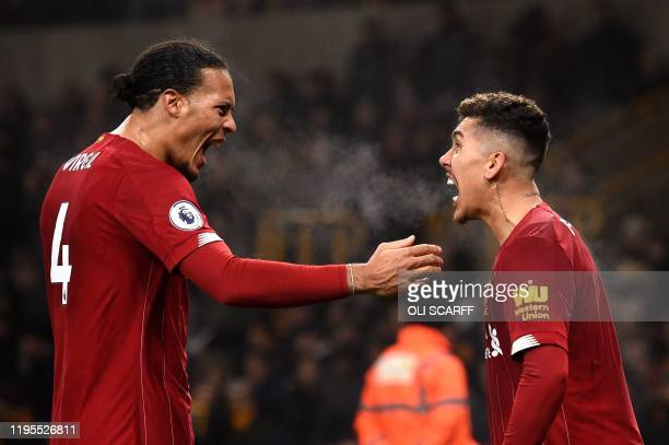 TOPSHOT Liverpool's Brazilian midfielder Roberto Firmino celebrates with teammates after he scores the team's second goal during the English Premier...