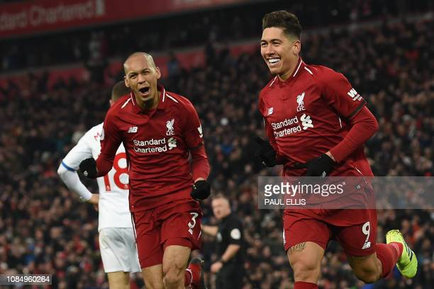 Liverpool's Brazilian midfielder Roberto Firmino celebrates with Liverpool's Brazilian midfielder Fabinho after scoring their second goal during the...