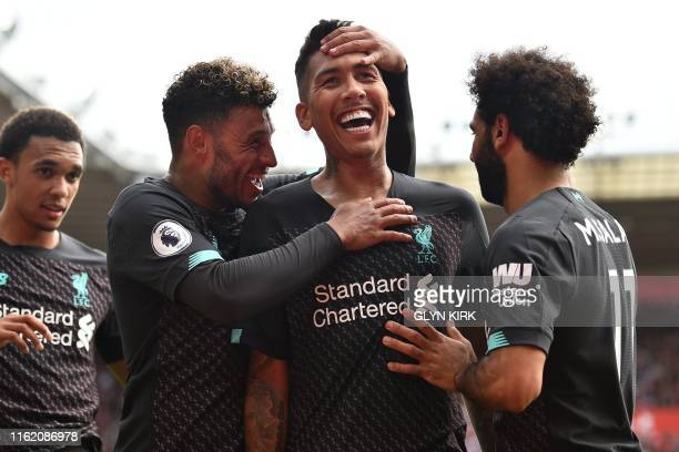 Liverpool's Brazilian midfielder Roberto Firmino celebrates with teammates after scoring their second goal during the English Premier League football...