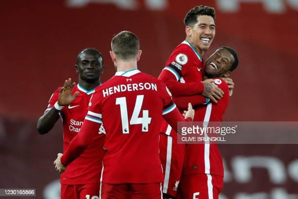Liverpool's Brazilian midfielder Roberto Firmino celebrates with Liverpool's Dutch midfielder Georginio Wijnaldum , Liverpool's Senegalese striker...