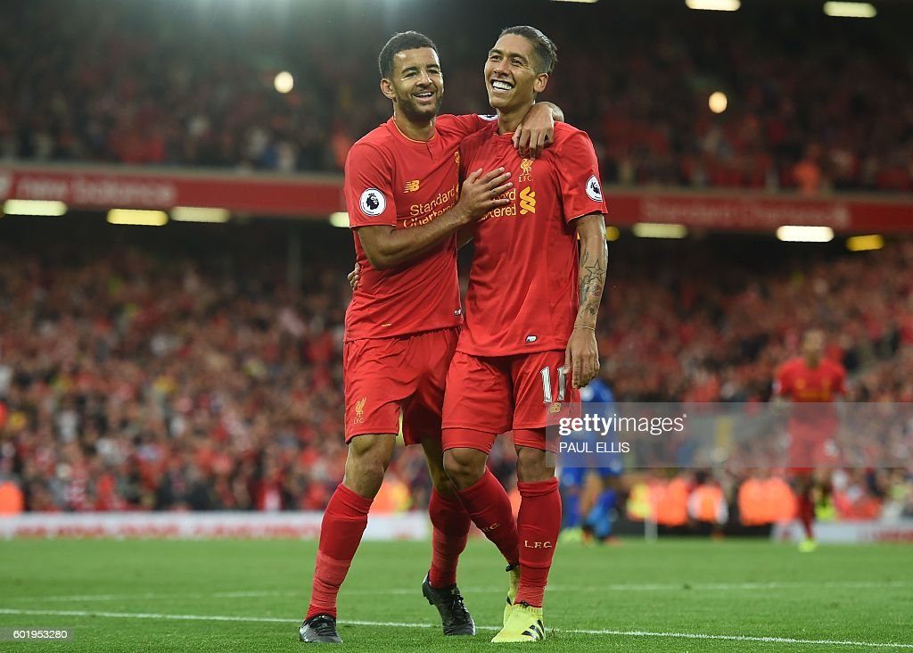 Liverpool's Brazilian midfielder Roberto Firmino (R) celebrates with Liverpool's English defender Kevin Stewart after scoring their fourth goal during the English Premier League football match between Liverpool and Leicester City at Anfield in Liverpool, north west England on September 10, 2016. / AFP / Paul ELLIS / RESTRICTED TO EDITORIAL USE. No use with unauthorized audio, video, data, fixture lists, club/league logos or 'live' services. Online in-match use limited to 75 images, no video emulation. No use in betting, games or single club/league/player publications. /