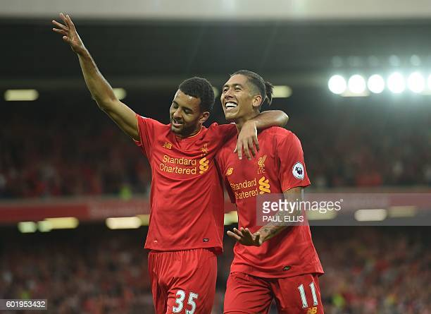 Liverpool's Brazilian midfielder Roberto Firmino celebrates with Liverpool's English defender Kevin Stewart after scoring their fourth goal during...