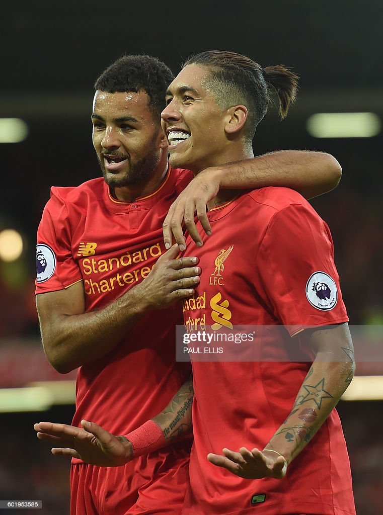 Liverpool's Brazilian midfielder Roberto Firmino (R) celebrates with Liverpool's English defender Kevin Stewart after scoring their fourth goal during the English Premier League football match between Liverpool and Leicester City at Anfield in Liverpool, north west England on September 10, 2016. Liverpool won the game 4-1. / AFP / Paul ELLIS / RESTRICTED TO EDITORIAL USE. No use with unauthorized audio, video, data, fixture lists, club/league logos or 'live' services. Online in-match use limited to 75 images, no video emulation. No use in betting, games or single club/league/player publications. /