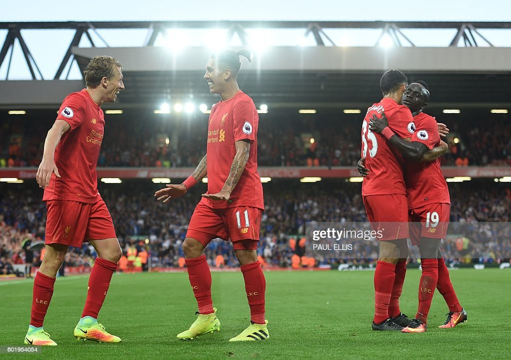 Liverpool's Brazilian midfielder Roberto Firmino (2nd L) celebrates with Liverpool's Brazilian midfielder Lucas Leiva (L) as Liverpool's English defender Kevin Stewart embraces Liverpool's Senegalese midfielder Sadio Mane (R) after Firmino scores their fourth goal during the English Premier League football match between Liverpool and Leicester City at Anfield in Liverpool, north west England on September 10, 2016. Liverpool won the game 4-1. / AFP / Paul ELLIS / RESTRICTED TO EDITORIAL USE. No use with unauthorized audio, video, data, fixture lists, club/league logos or 'live' services. Online in-match use limited to 75 images, no video emulation. No use in betting, games or single club/league/player publications. /