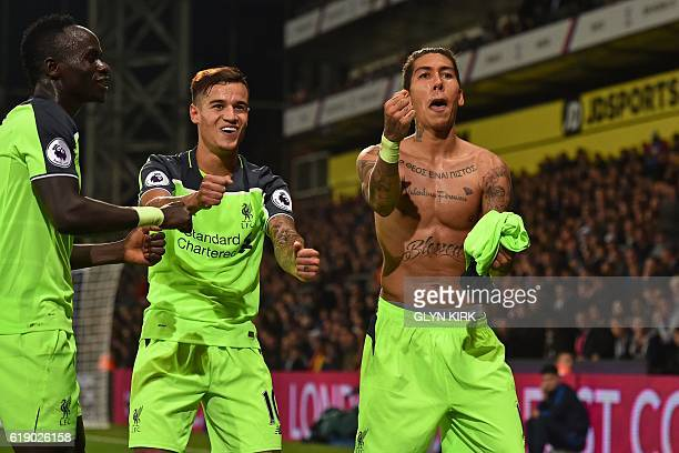 Liverpool's Brazilian midfielder Roberto Firmino celebrates with Liverpool's Senegalese midfielder Sadio Mane and Liverpool's Brazilian midfielder...