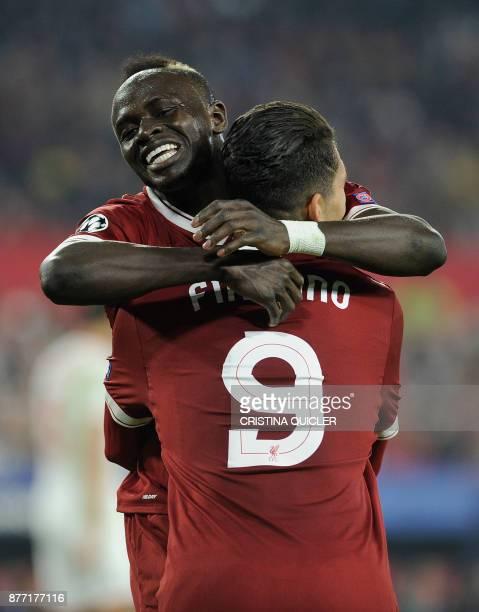 Liverpool's Brazilian midfielder Roberto Firmino celebrates with Liverpool's Senegalese midfielder Sadio Mane after scoring a goal on November 21...