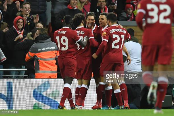 Liverpool's Brazilian midfielder Roberto Firmino celebrates with teammates after scoring the opening goal of the English FA Cup fourth round football...