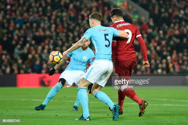 Liverpool's Brazilian midfielder Roberto Firmino chips the ball up to score their second goal to take the lead 21 during the English Premier League...