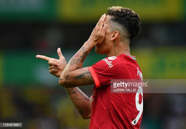 Liverpool's Brazilian midfielder Roberto Firmino gestures with his finger in the shape of a gun as he celebrates scoring his team's second goal...