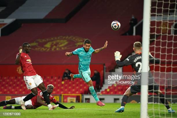 Liverpool's Brazilian midfielder Roberto Firmino heads past Manchester United's English goalkeeper Dean Henderson for their second goal during the...