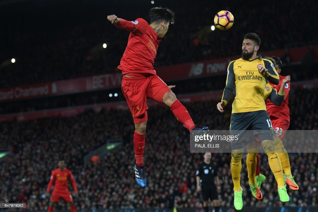 Liverpool's Brazilian midfielder Roberto Firmino (C) heads the ball across goal during the English Premier League football match between Liverpool and Arsenal at Anfield in Liverpool, north west England on March 4, 2017. Liverpool won the game 3-1. / AFP PHOTO / Paul ELLIS / RESTRICTED TO EDITORIAL USE. No use with unauthorized audio, video, data, fixture lists, club/league logos or 'live' services. Online in-match use limited to 75 images, no video emulation. No use in betting, games or single club/league/player publications. /