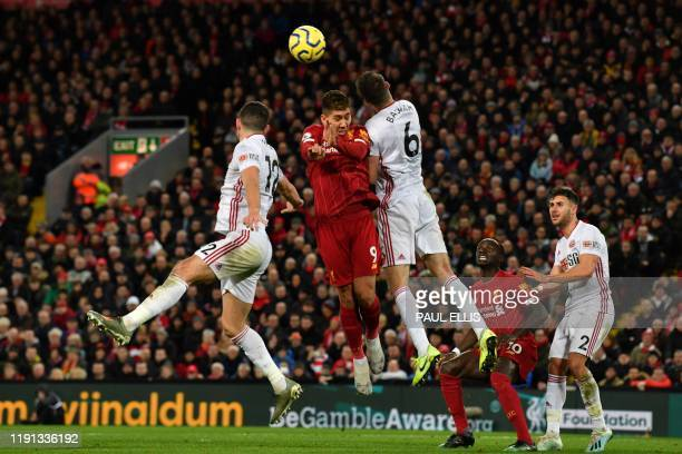 TOPSHOT Liverpool's Brazilian midfielder Roberto Firmino heads the ball during the English Premier League football match between Liverpool and...