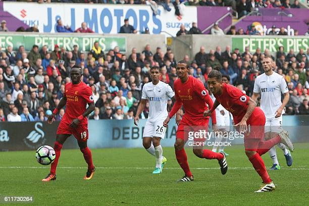 Liverpool's Brazilian midfielder Roberto Firmino heads the ball to score their first goal to equalise 1-1 during the English Premier League football...