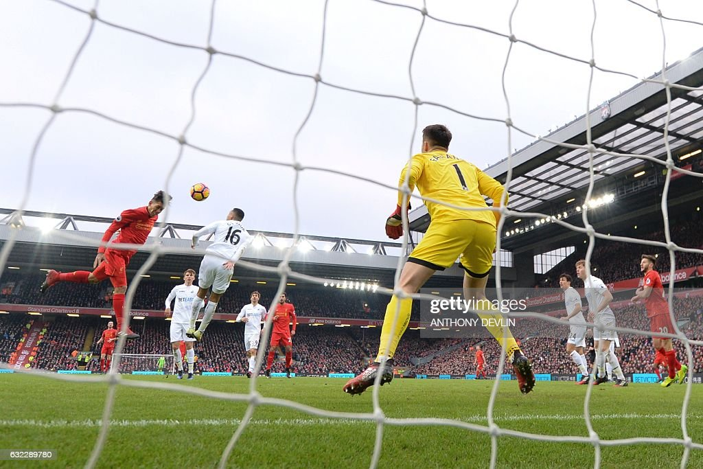 Liverpool's Brazilian midfielder Roberto Firmino (L) heads the ball to score their first goal during the English Premier League football match between Liverpool and Swansea City at Anfield in Liverpool, north west England on January 21, 2017. / AFP / Anthony DEVLIN / RESTRICTED TO EDITORIAL USE. No use with unauthorized audio, video, data, fixture lists, club/league logos or 'live' services. Online in-match use limited to 75 images, no video emulation. No use in betting, games or single club/league/player publications. /