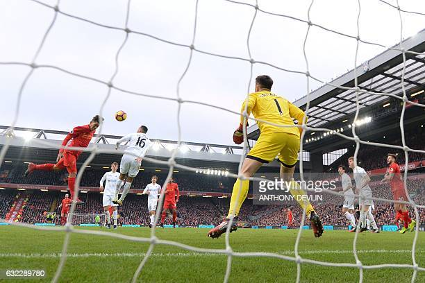 Liverpool's Brazilian midfielder Roberto Firmino heads the ball to score their first goal during the English Premier League football match between...