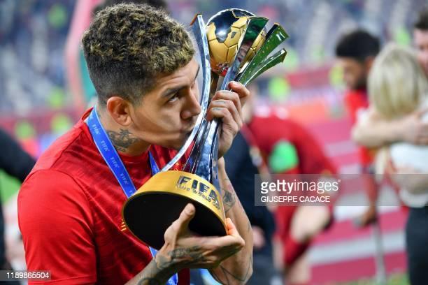 Liverpool's Brazilian midfielder Roberto Firmino kisses the trophy following the 2019 FIFA Club World Cup Final football match between England's...