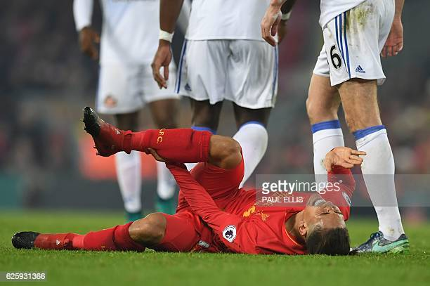 Liverpool's Brazilian midfielder Roberto Firmino lies injured on the pitch during the English Premier League football match between Liverpool and...