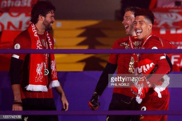 Liverpool's Brazilian midfielder Roberto Firmino Liverpool's Spanish goalkeeper Adrian and Liverpool's Brazilian goalkeeper Alisson Becker recieve...