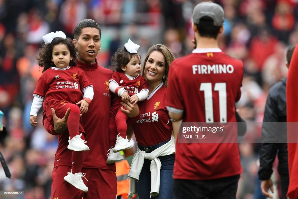 Liverpool's Brazilian midfielder Roberto Firmino poses with children for a photograph following the English Premier League football match between Liverpool and Middlesbrough at Anfield in Liverpool, north west England on May 21, 2017. Liverpool won the match 3-0. / AFP PHOTO / Paul ELLIS / RESTRICTED TO EDITORIAL USE. No use with unauthorized audio, video, data, fixture lists, club/league logos or 'live' services. Online in-match use limited to 75 images, no video emulation. No use in betting, games or single club/league/player publications. /