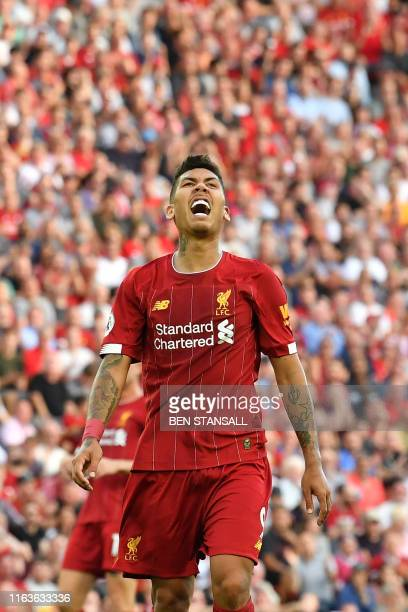 Liverpool's Brazilian midfielder Roberto Firmino reacts after missing a chance during the English Premier League football match between Liverpool and...