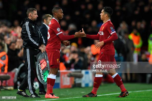 Liverpool's Brazilian midfielder Roberto Firmino shakes hands with Liverpool's English striker Daniel Sturridge as Firmino is substituted during the...