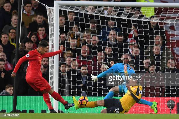Liverpool's Brazilian midfielder Roberto Firmino shoots past Arsenal's Czech goalkeeper Petr Cech to score the opening goal of the English Premier...