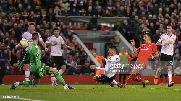 Liverpool's Brazilian midfielder Roberto Firmino shoots past Manchester United's Spanish goalkeeper David de Gea to score his team's second goal...