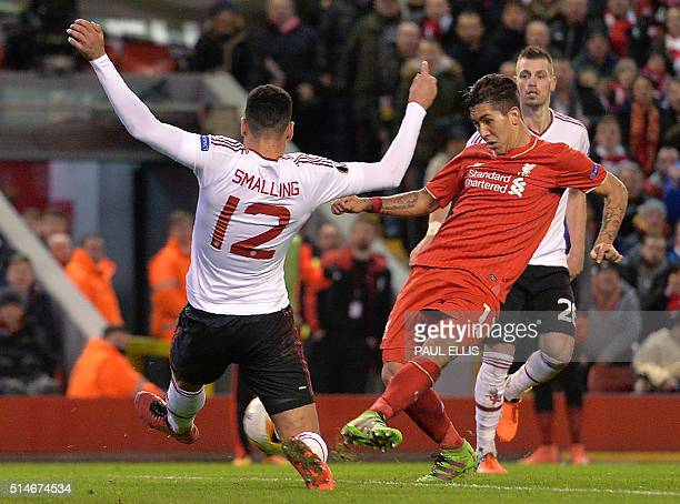 Liverpool's Brazilian midfielder Roberto Firmino shoots past Manchester United's English defender Chris Smalling to score his team's second goal...