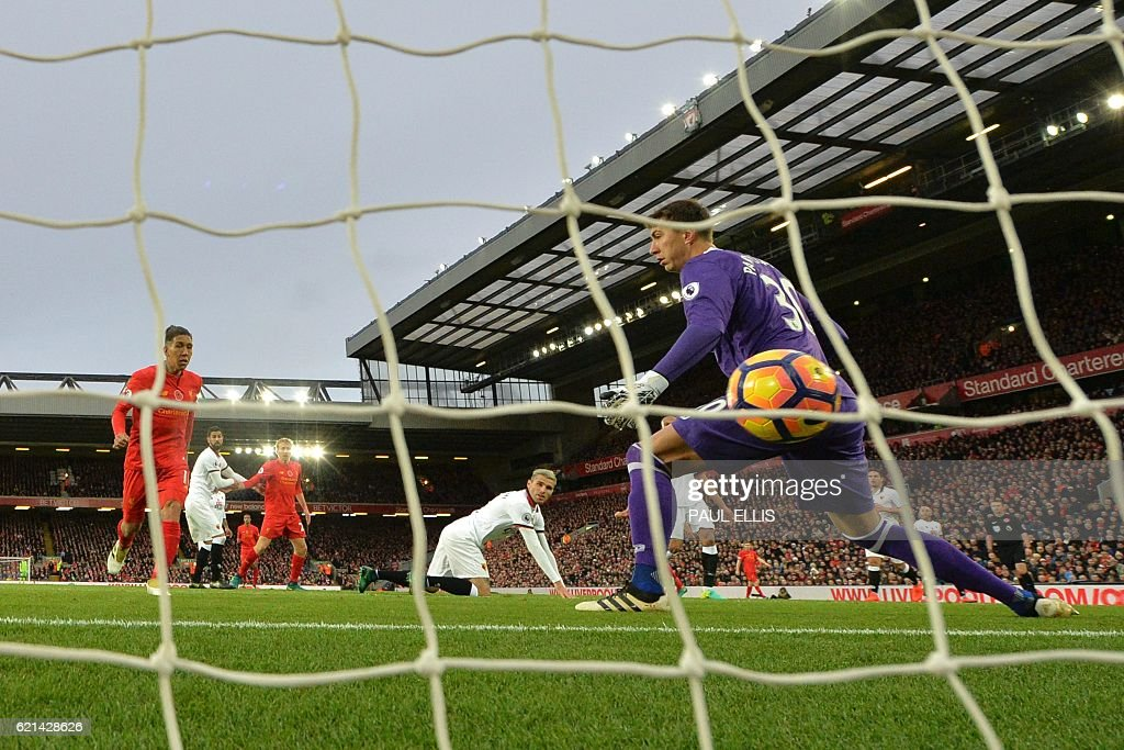 Liverpool's Brazilian midfielder Roberto Firmino (L) shoots past Watford's Romanian goalkeeper Costel Pantilimon to score his team's fourth goal during the English Premier League football match between Liverpool and Watford at Anfield in Liverpool, north west England on November 6, 2016. / AFP / PAUL ELLIS / RESTRICTED TO EDITORIAL USE. No use with unauthorized audio, video, data, fixture lists, club/league logos or 'live' services. Online in-match use limited to 75 images, no video emulation. No use in betting, games or single club/league/player publications. /