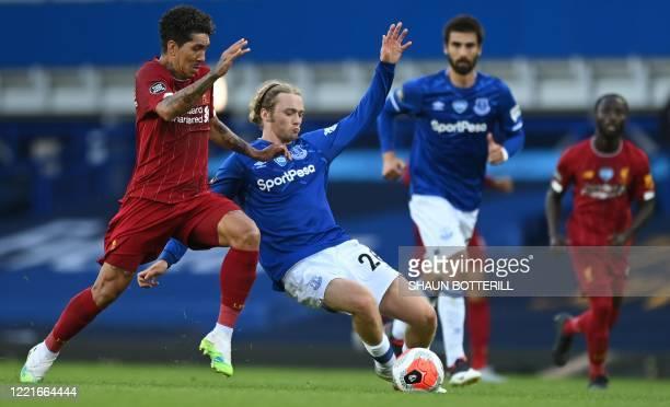 Liverpool's Brazilian midfielder Roberto Firmino tackles Everton's English midfielder Tom Davies during the English Premier League football match...
