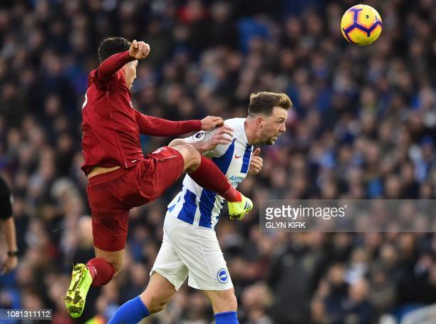 Liverpool's Brazilian midfielder Roberto Firmino vies with Brighton's English midfielder Dale Stephens during the English Premier League football...