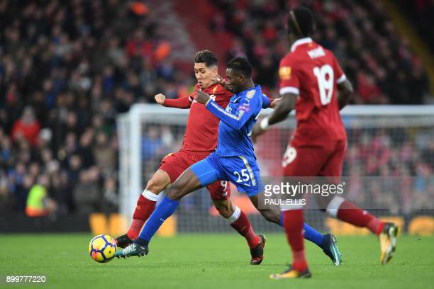 Liverpool's Brazilian midfielder Roberto Firmino vies with Leicester City's Nigerian midfielder Wilfred Ndidi during the English Premier League...