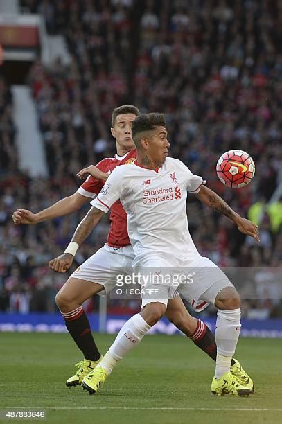 Liverpool's Brazilian midfielder Roberto Firmino vies with Manchester United's Spanish midfielder Ander Herrera during the English Premier League...