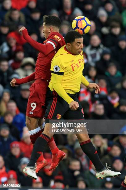 Liverpool's Brazilian midfielder Roberto Firmino vies with Watford's English striker Troy Deeney during the English Premier League football match...