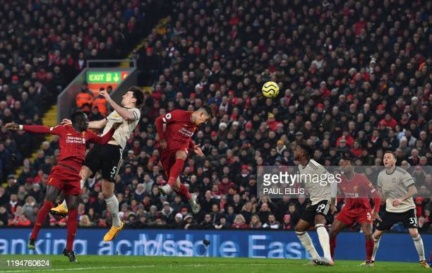 Liverpool's Brazilian midfielder Roberto Firmino wins the ball in the air against Manchester United's English defender Harry Maguire during the...