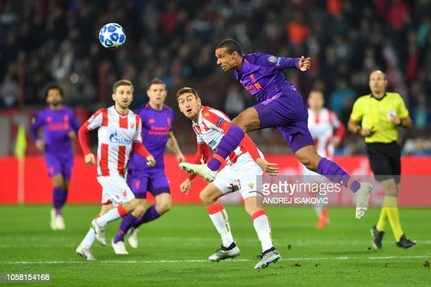 Liverpool's Cameroonian defender Joel Matip heads the ball flanked by Red Star Belgrade's Serbian midfielder Dusan Jovancic during the UEFA Champions...