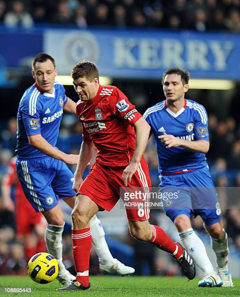 Liverpool's Captain Steven Gerrard runs with the ball past Chelsea's John Terry and Frank Lampard during the Premiership football match at Stamford...