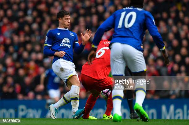 Liverpool's Croatian defender Dejan Lovren is fouled by Everton's English midfielder Ross Barkley who was subsequently booked during the English...