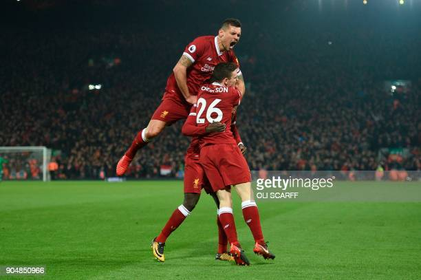 Liverpool's Croatian defender Dejan Lovren jumps in to celebrate their third goal scored by Liverpool's Senegalese midfielder Sadio Mane to extend...