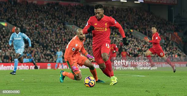 Liverpool's Daniel Sturridge goes around Stoke City's goalkeeper Lee Grant to score his sides fourth goal during the Premier League match between...