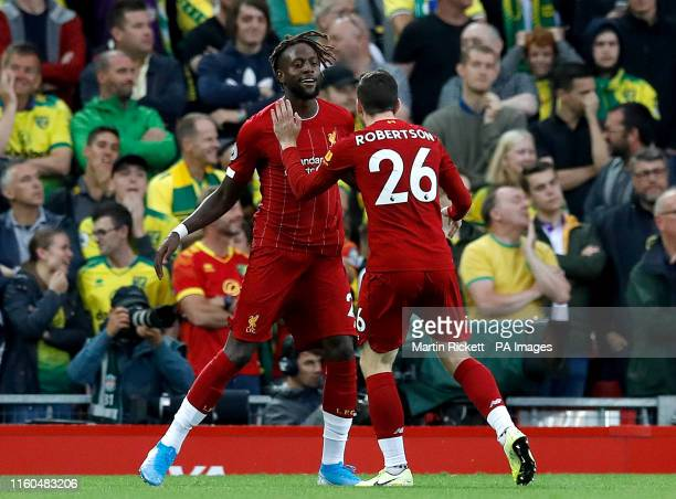 Liverpool's Divock Origi celebrates with team-mate Andrew Robertson after his cross is turned in by Norwich City's Grant Hanley for the first goal of...