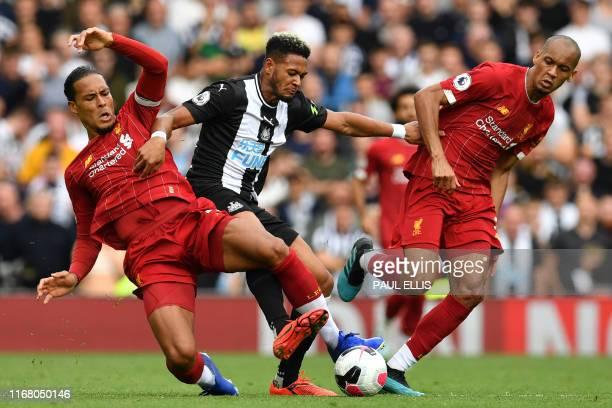 TOPSHOT Liverpool's Dutch defender Virgil van Dijk and Liverpool's Brazilian midfielder Fabinho tackle Newcastle United's Brazilian striker Joelinton...