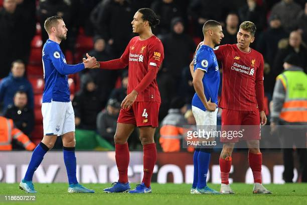 Liverpool's Dutch defender Virgil van Dijk and Liverpool's Brazilian midfielder Roberto Firmino comiserate Everton's Icelandic midfielder Gylfi...