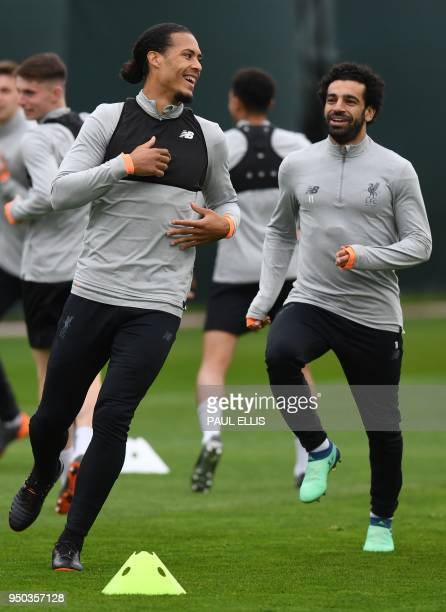 Liverpool's Dutch defender Virgil van Dijk and Liverpool's Egyptian midfielder Mohamed Salah attends a training session at the team's Melwood...