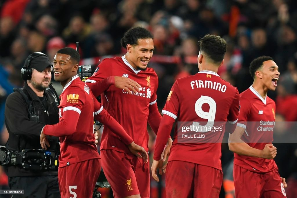 Liverpool's Dutch defender Virgil van Dijk (C) celebrates with Liverpool's Brazilian midfielder Roberto Firmino (2R) at the end of the English FA Cup third round football match between Liverpool and Everton at Anfield in Liverpool, north west England on January 5, 2018. / AFP PHOTO / Paul ELLIS / RESTRICTED TO EDITORIAL USE. No use with unauthorized audio, video, data, fixture lists, club/league logos or 'live' services. Online in-match use limited to 75 images, no video emulation. No use in betting, games or single club/league/player publications. /