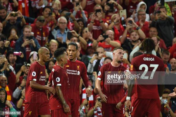Liverpool's Dutch defender Virgil van Dijk celebrates with teammates after he scores the team's third goal during the English Premier League football...