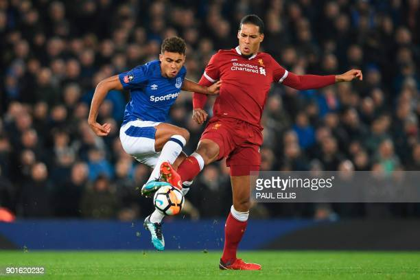 Liverpool's Dutch defender Virgil van Dijk challenges Everton's English defender Mason Holgate during the English FA Cup third round football match...